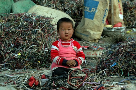 "The Greenpeace caption: ""A Chinese child sits amongst a pile of wires and e-waste. Children can often be found dismantling e-waste containing many hazardous chemicals known to be potentially very damaging to children's health."""